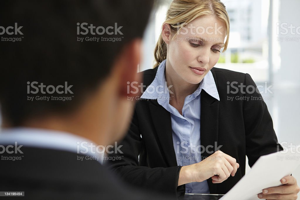 A woman interviewer asking a prospect about his resume royalty-free stock photo