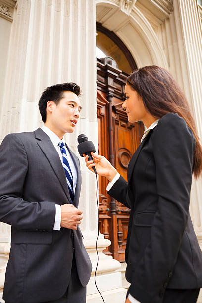 Woman Interviews Man A reporter with a microphone interviews a well dressed man. Could be politician, businessman, government official, or spokesperson. spokesperson stock pictures, royalty-free photos & images