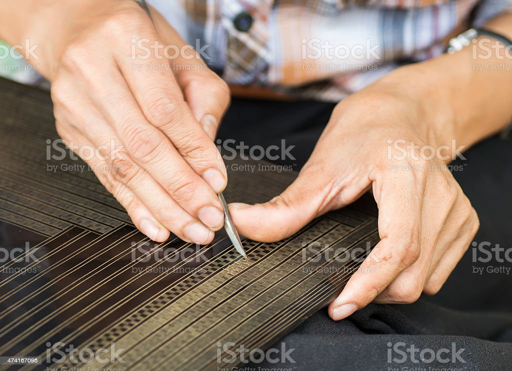 Woman Intricately Etching Lacquerware Closeup stock photo