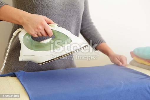 istock Woman ironing blue polo shirt 473498154