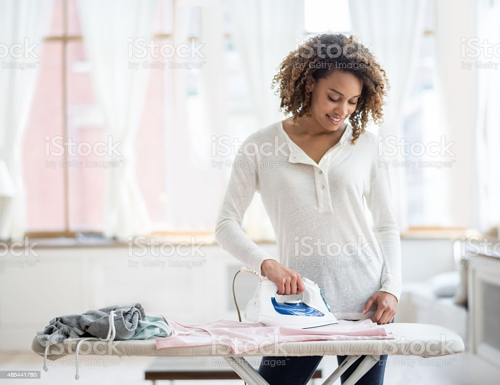 Woman ironing clothes at home stock photo