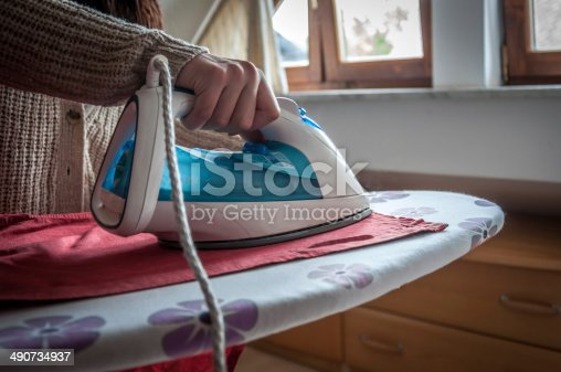 524159504 istock photo Woman ironing clothes 490734937