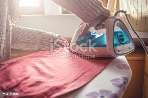 524159504 istock photo Woman ironing clothes 524159504