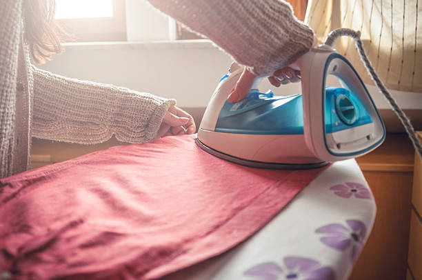 woman ironing clothes - ironing stock photos and pictures