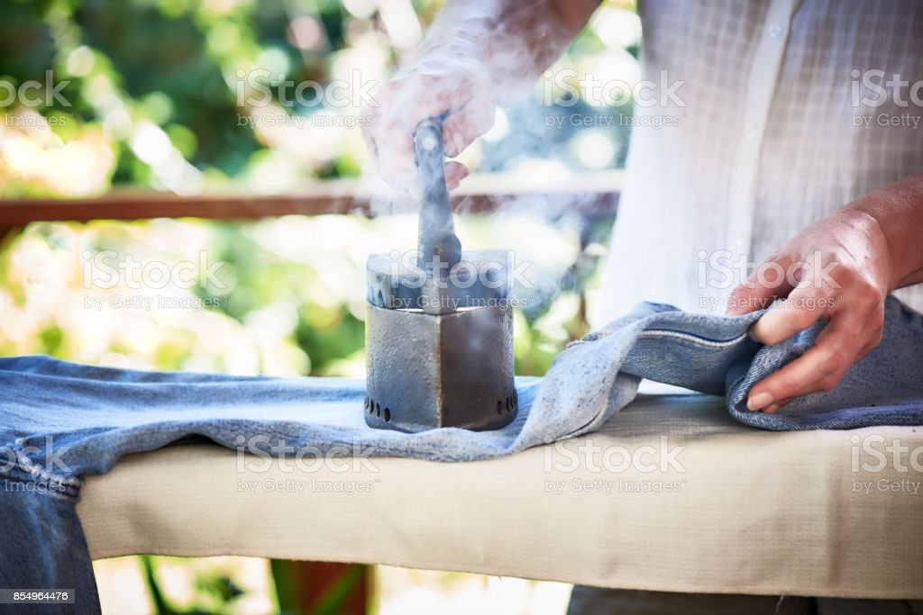 woman ironing jeans at home on sunlit terrace with a ancient iron stock photo