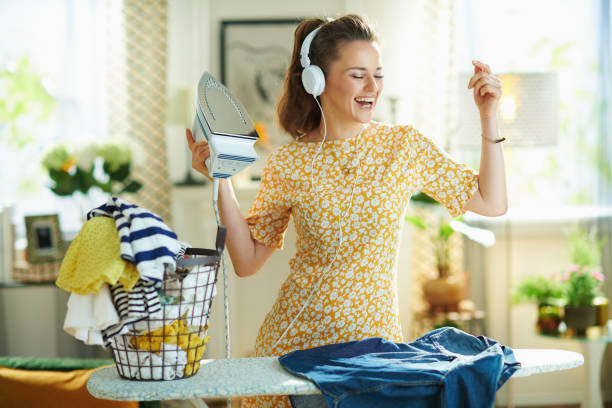 woman ironing on ironing board while listening to the music stock photo