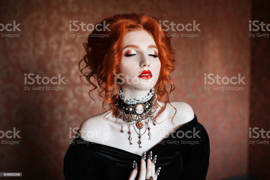 A woman is a vampire with pale skin and red hair in a black dress and a necklace on her neck. Girl witch with vampire claws and red lips. Gothic look. Outfit for halloween. stock photo