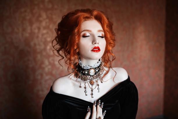 eine frau ist ein vampir mit blasse haut und rote haare in ein schwarzes kleid und eine kette an ihrem hals. mädchen hexe vampir krallen und roten lippen. gotische aussehen. outfit für halloween. - gothic kleid stock-fotos und bilder