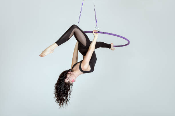 woman is an acrobat in a hula hoopa. - equilibrista foto e immagini stock