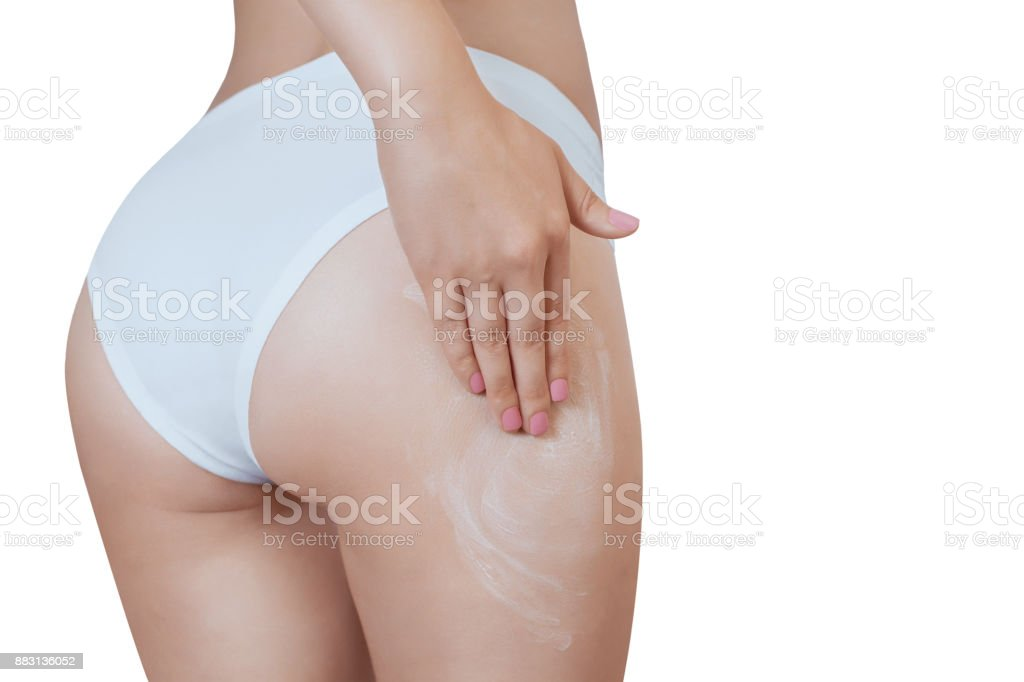 A woman is applying an anti-cellulite cream on her ass. stock photo