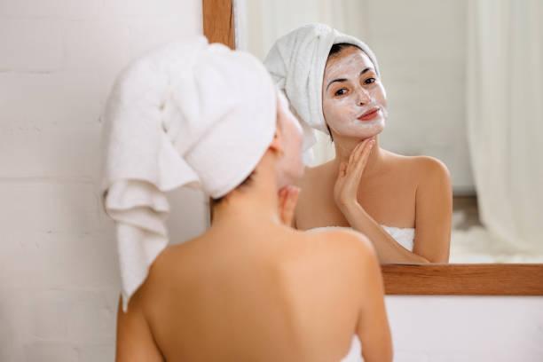 vrouw is het aanbrengen van masker op haar gezicht - mirror mask stockfoto's en -beelden