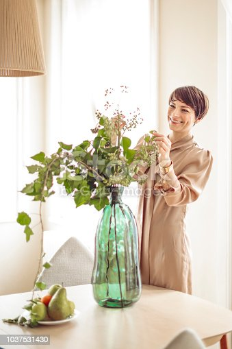 Woman is arranging her flowers at home