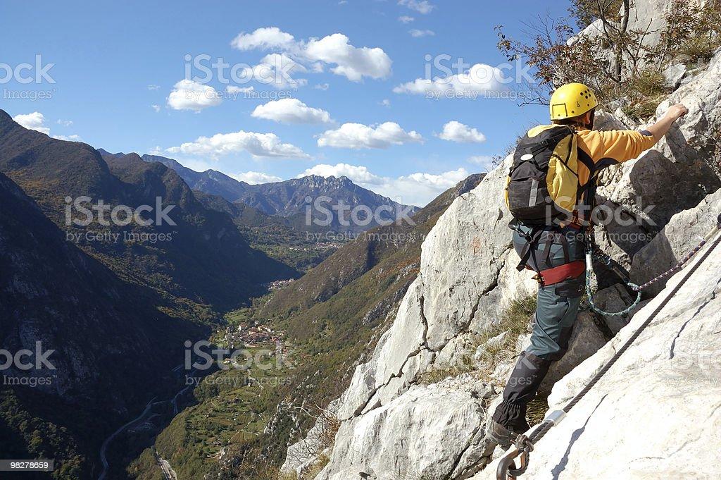 Woman is ascending the mountain via ferrata royalty-free stock photo