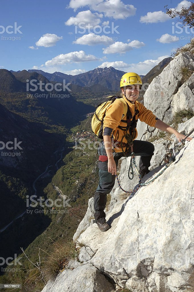 Woman is ascending the mountain via ferrata royalty-free stock photo