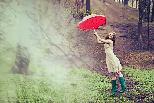 A woman is blown away with her red dotted umbrella in forest.
