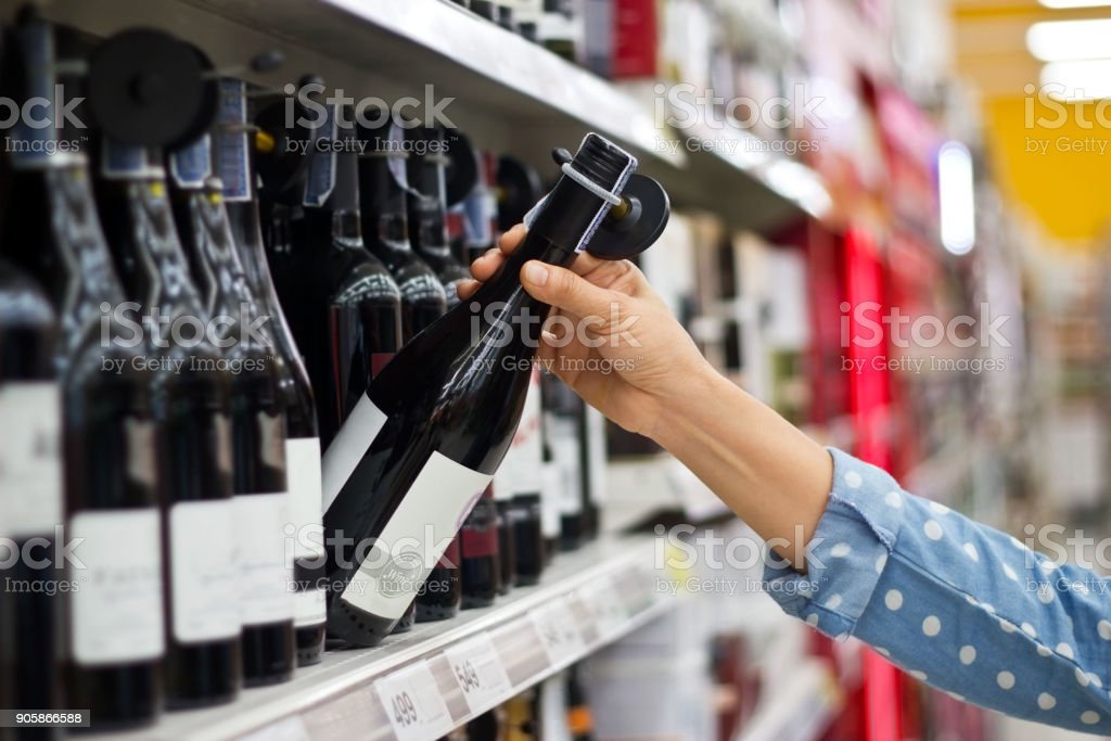 Woman is buying a bottle of wine at the supermarket background stock photo