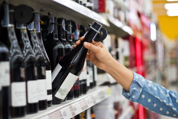Woman is buying a bottle of wine at the supermarket background - foto stock