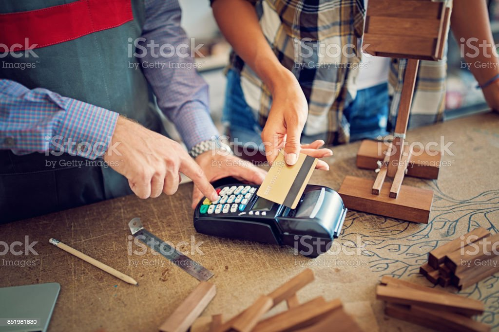 Woman is buying a wooden lamp and paying in a small family carpenter factory stock photo