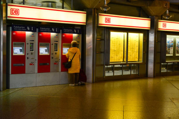 Woman is buying tickets in a ticket machine at the railway station Munchen Hauptbahnhof stock photo
