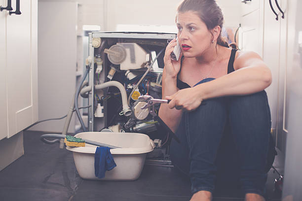 Woman is calling a plumber to repair the leak stock photo