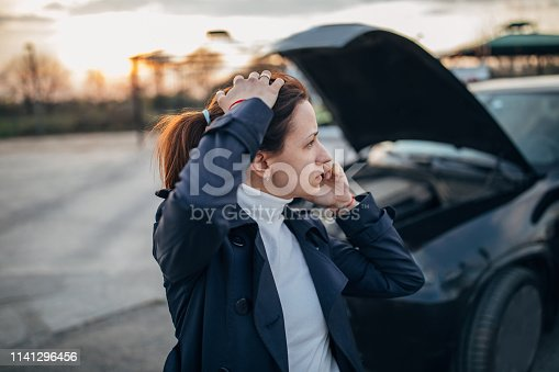 Young, stressed woman is calling emergency service  to help her with a broken car.