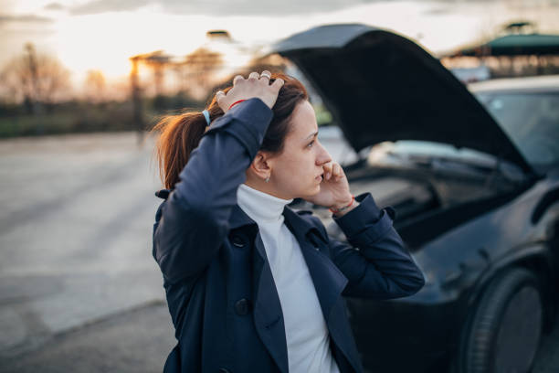 Woman is calling emergency service to help her with a broken car stock photo