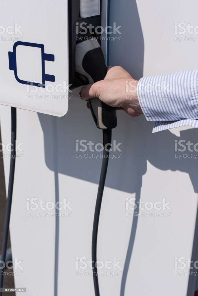 Woman is charging her electric vehicle with a charging cable