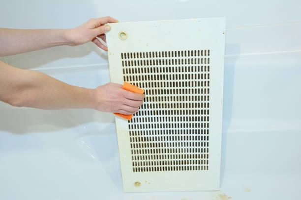 Een vrouw is het schoonmaken van een capture panel van een keuken kap, range hood, afzuigkap van vet met een spons, en een wasmiddel. foto