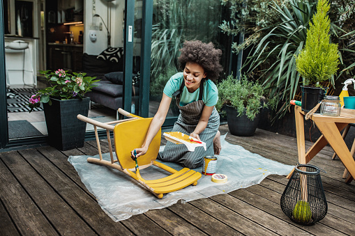 Female artist painting vintage chair in yellow color with a paintbrush in the back yard