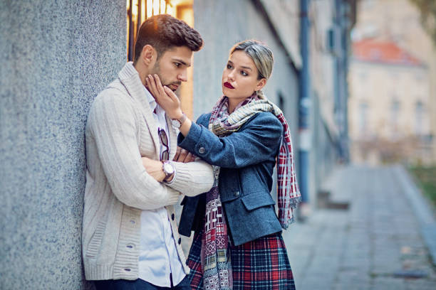 Woman is consoling her sulking boyfriend on the street stock photo