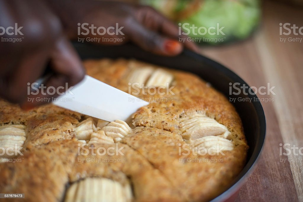 Woman is cutting a piece of apple cake stock photo