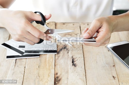 istock woman is cutting credit card with scissors 826319704