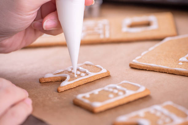 Woman is decorating gingerbread cookies house with white frosting icing cream topping on wooden table background, baking paper in kitchen, close up, macro. Woman is decorating gingerbread cookies house with white frosting icing cream topping on wooden table background, baking paper in kitchen, close up, macro. icing bag stock pictures, royalty-free photos & images