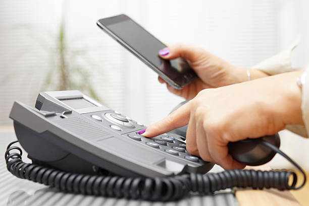 Woman is dialing on land line phone and looking on mobile phone Woman is dialing on land line phone and looking on mobile phone telephone directory stock pictures, royalty-free photos & images
