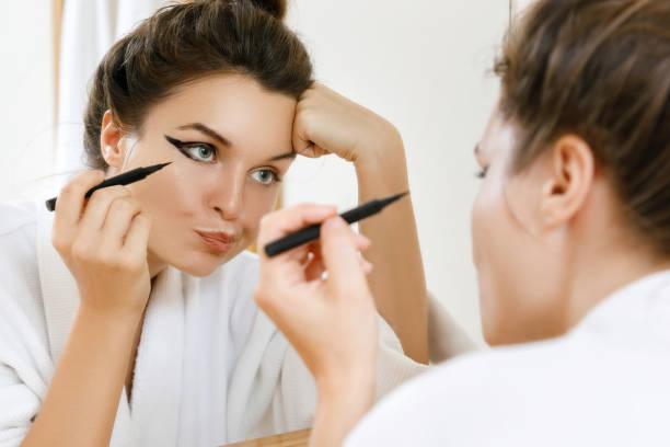 frau ist enttäuscht von ihrer fähigkeit, make-up anzuwenden - natürliche make up kurse stock-fotos und bilder