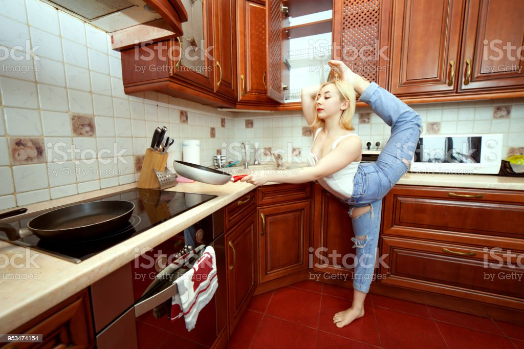 Woman is doing gymnastics in the kitchen. stock photo