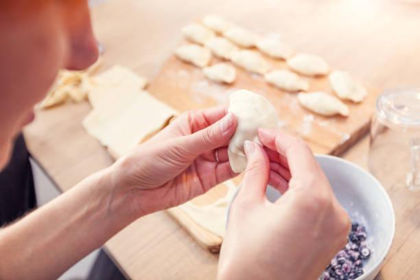 frau tut hand knödel mit heidelbeeren - knödel kochen stock-fotos und bilder