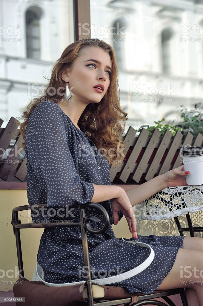 Woman is drinking coffee in an outdoor cafe foto de stock royalty-free