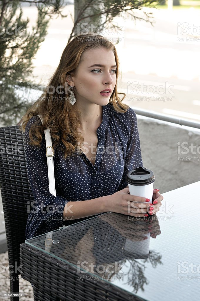 Woman is drinking coffee in an outdoor cafe zbiór zdjęć royalty-free