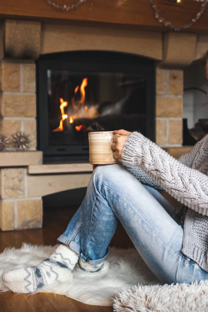 Woman is drinking hot drink in front of fireplace at home interior. stock photo