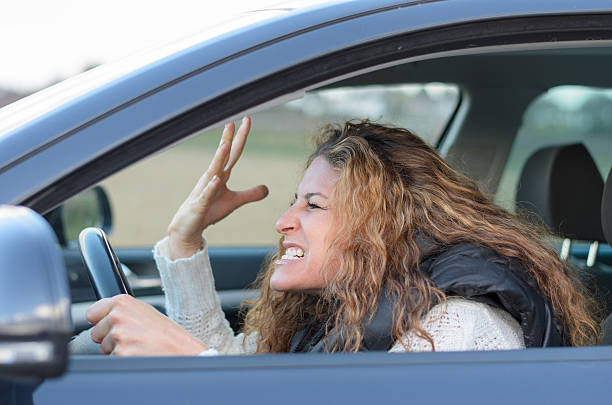 woman is driving her car - swearing stockfoto's en -beelden
