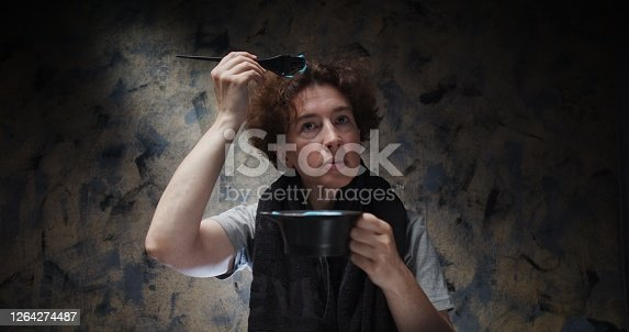Woman is dyeing her own hair in blue