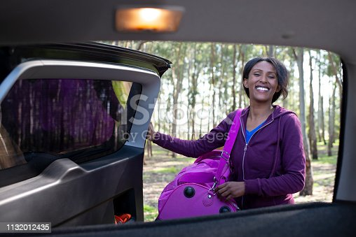 812419994istockphoto Woman is excited after arriving to her vacation destination. The woman unpacking luggage from the car trunk, closing the rear door. 1132012435