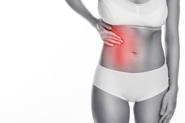 Woman is feeling pain under her ribs Woman is feeling pain under her ribs. Liver problem. Isolated on white background human rib cage stock pictures, royalty-free photos & images