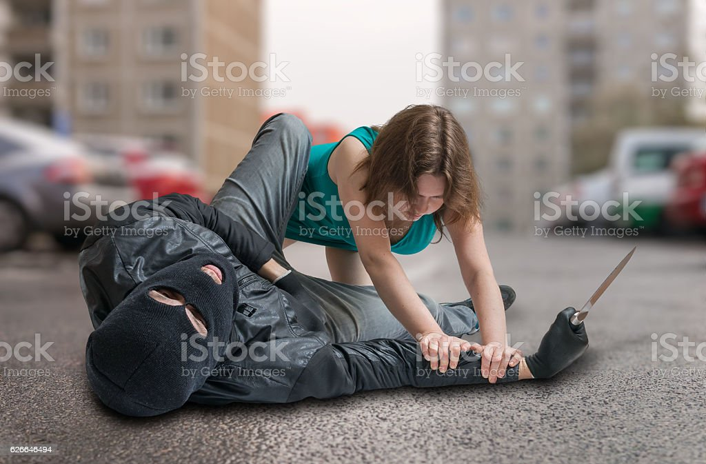 Woman is fighting with thief on street. Self defense concept. stock photo