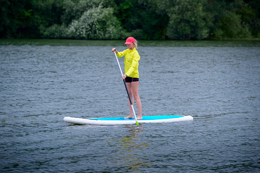 A woman is floating on a SUP board along a large river. Stand on the paddle boarding - amazing outdoor activities
