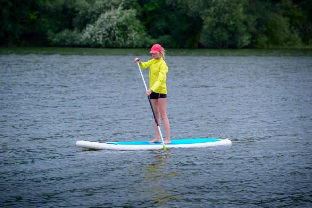 Een vrouw zweeft op een SUP Board langs een grote rivier. Sta op de paddle boarding-geweldige outdoor activiteiten foto