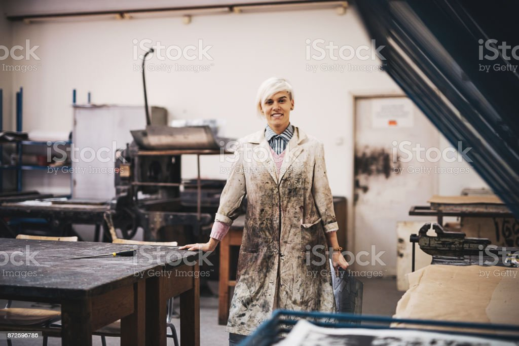 Woman is focused on artwork and atching production in her studio stock photo
