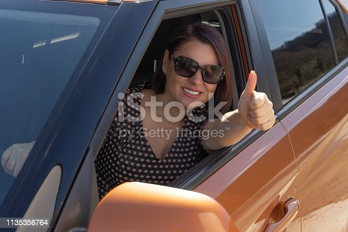 Woman is gesturing thumbs up sitting inside a new suv.