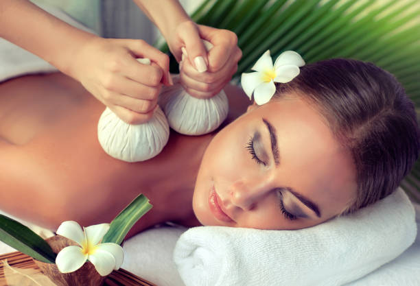woman is getting massage in the spa salon. - thai massage stock photos and pictures